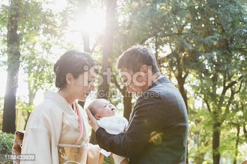 Japanese father in his 50's wearing suits and mother in her 40's wearing kimono celebrating the birth of their new born baby.