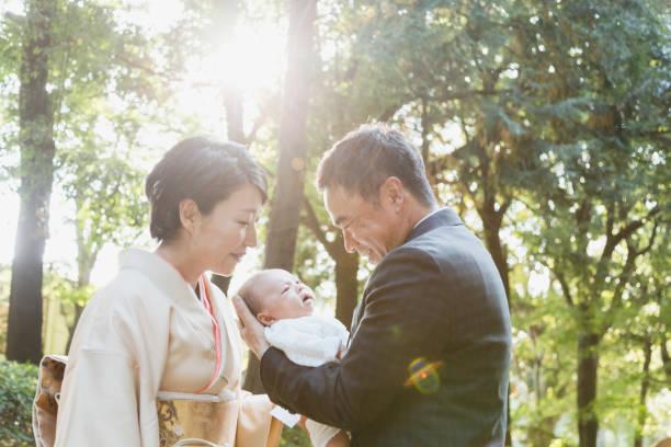 Pares maduros japoneses que desgastam o desgaste formal que carreg seu bebê recém-nascido - foto de acervo