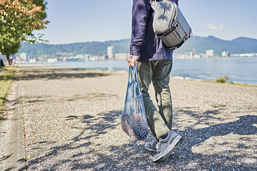 Japanese men are incorporating reusable cotton mesh bags into their daily lives. On the boardwalk overlooking Lake Biwa in Shiga Prefecture.