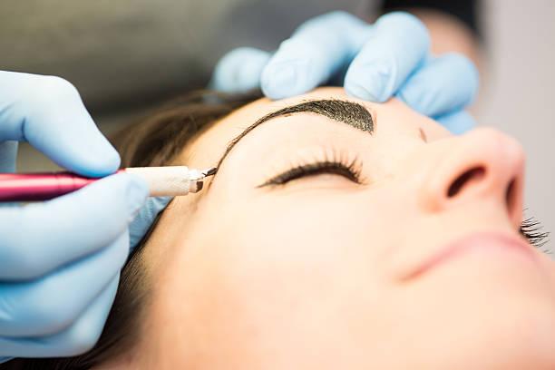 japanische methode zieht augenbrauen, nahaufnahme, brünett im schönheits-salon - tattoo ideen stock-fotos und bilder