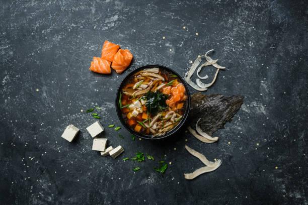 豆腐と成分とビンテージ色付きの背景上に黒ボウルに鮭の味噌スープ。トップ ビュー ストックフォト