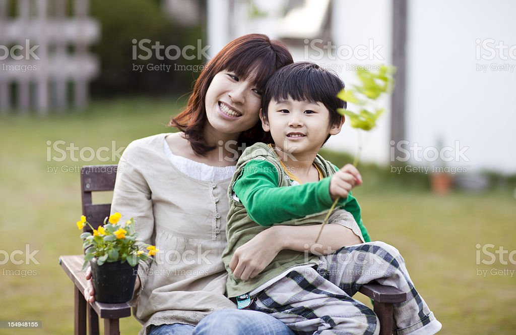 Japanese Mom And Son Enjoy Evening In A Garden Royalty Free Stock Photo
