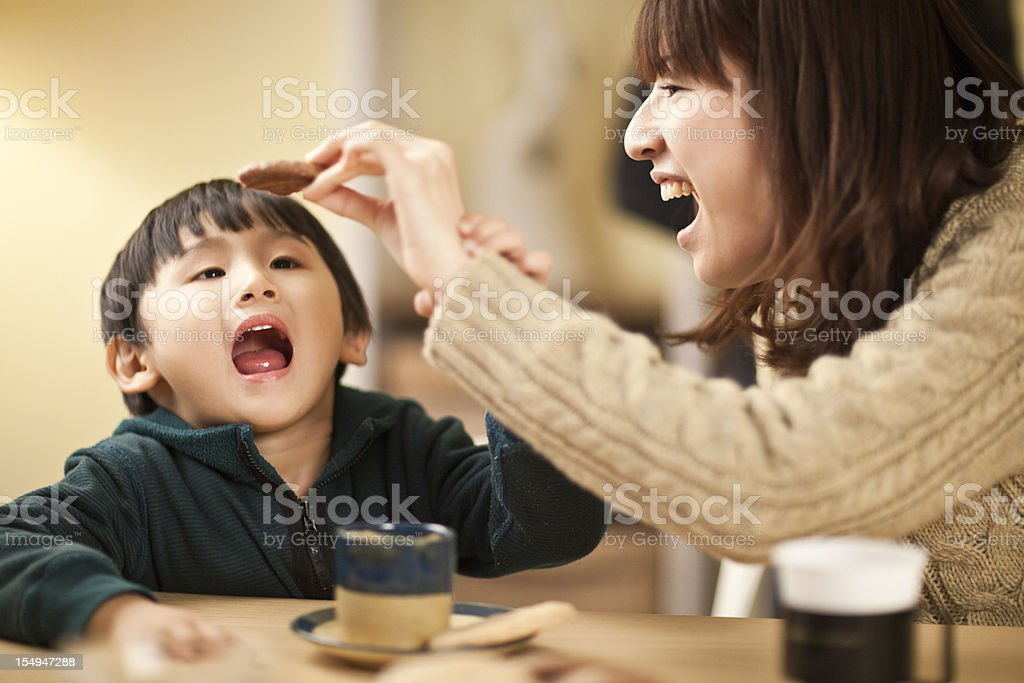 Japanese Mom And Son Playing With Cookies At The Table Royalty Free Stock Photo