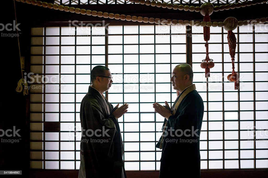 Japanese monks greeting each other at a temple - Religious concepts