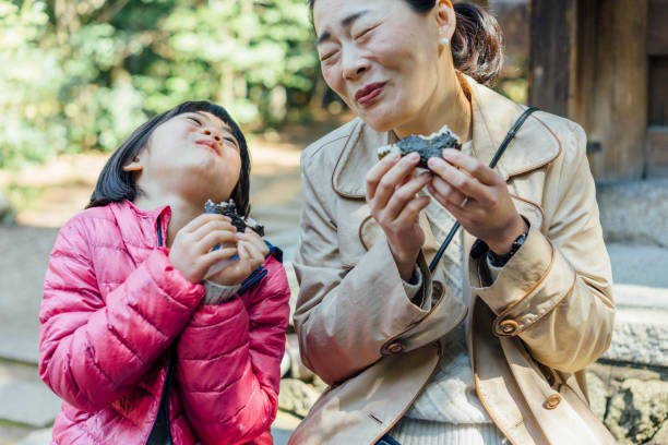Japanese mother and daughter eating onigiri together stock photo