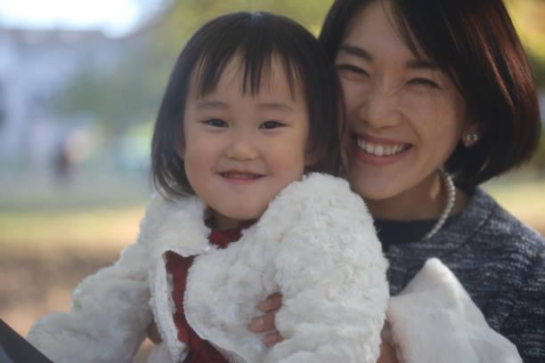 日本母親抱著她的女兒在石池去三慶典圖像檔