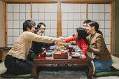 日本の部屋の食卓で、お飾ちりり、日本の新年料理を食べる前に乾杯を飲む日本のミューラ世代の家族