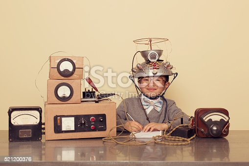 A young Japanese boy sits at office desk searching for successful ideas by using a mind reading helmet. He is working on ideas in the inner most parts of the brain. He is wearing a cardigan and bow tie.
