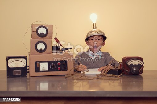 A young Japanese boy sits at office desk searching for successful ideas by using a homemade thinking cap with a lit up light bulb. He is working on ideas in the inner most parts of the brain and it looks like he has found an idea. He is wearing a cardigan and bow tie.
