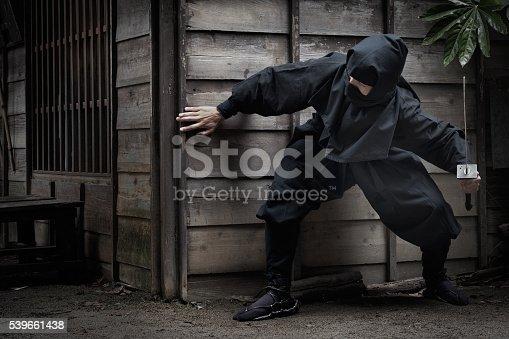 Kyoto iStockalypse.  A stealthy ninja (shinobi) draws his sword as he quietly peers behind the corner of a building in a rural village at night.  Toei Kyoto Studio Park.  Kyoto, Japan.