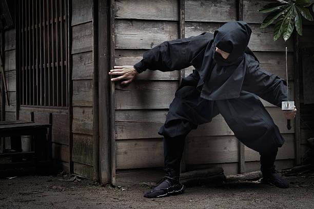 japonés ninja con espada escudan detrás de construcción listos para emboscada - ninja fotografías e imágenes de stock