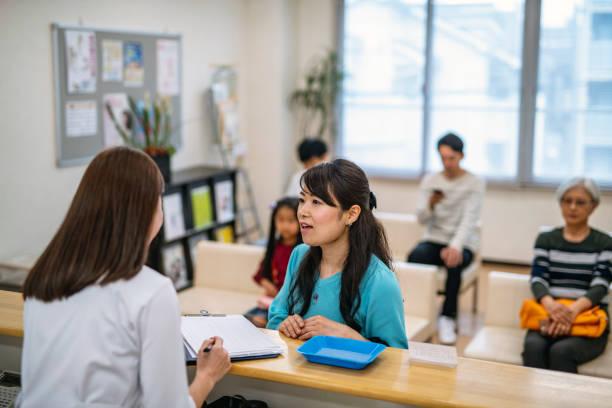 Japanische Krankenschwester unterstützt Patienten in Krankenhauswart-Zimmer – Foto