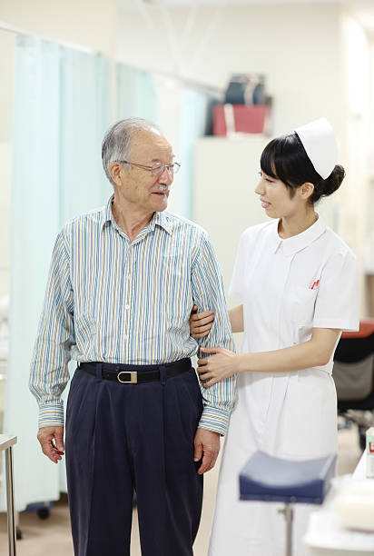 Japanese nurse assists elderly patient stock photo