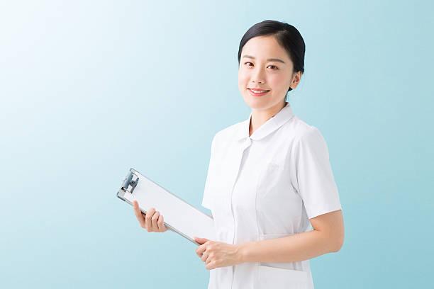 japanese nurse woman holding a clip board - 看護師 ストックフォトと画像