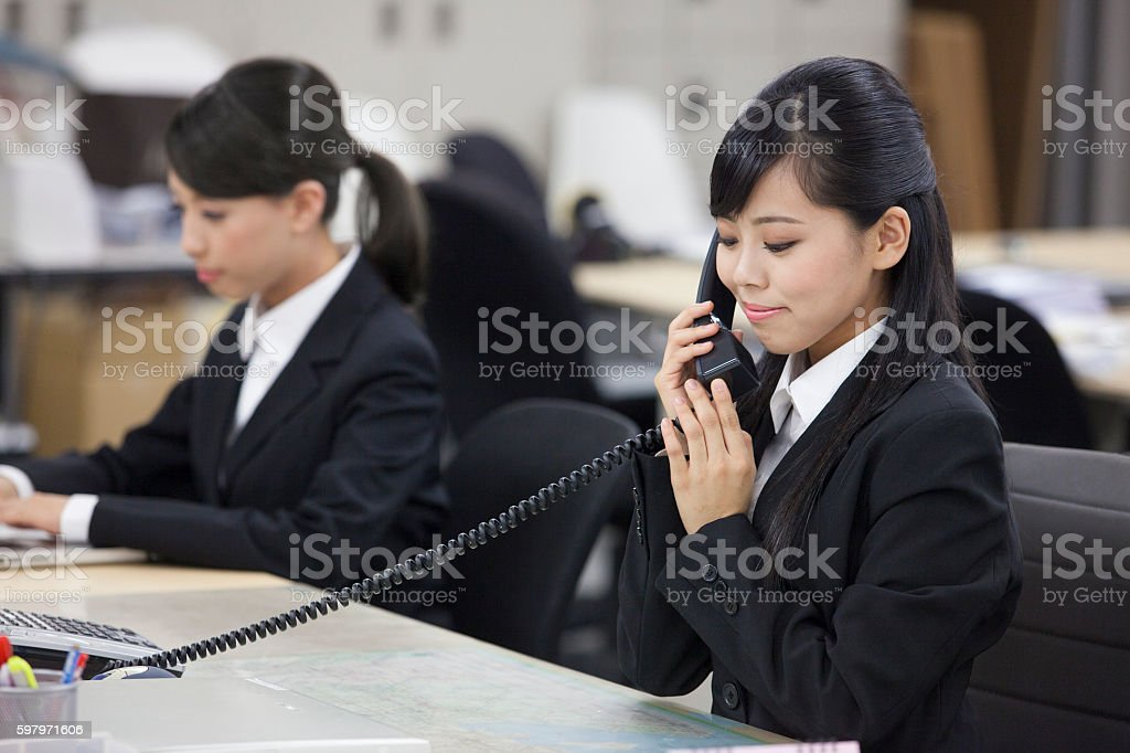 Japanese office employee answering phone stock photo