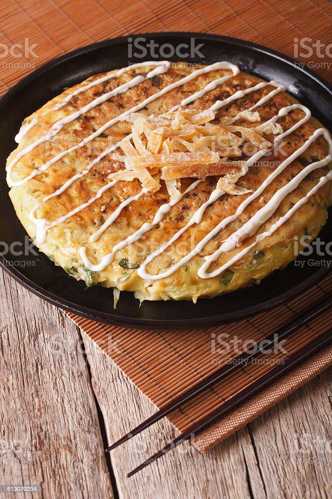 Japanese okonomiyaki on a table close-up and chopsticks. vertical stock photo
