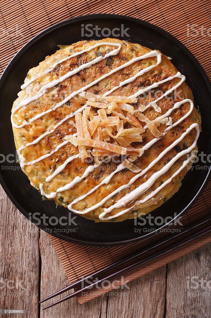 Japanese okonomiyaki on a table close-up. vertical top view stock photo