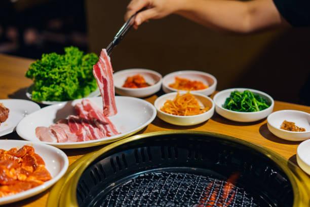 日本または韓国の焼肉スタイルのレストラン。ローストを持つ手の女性は、日本の焼肉牛肉のスライス。 - 韓国文化 ストックフォトと画像