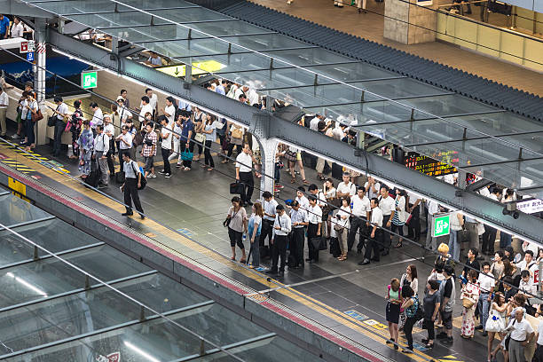 japanese people queue in train station in osaka - 通勤 ストックフォトと画像