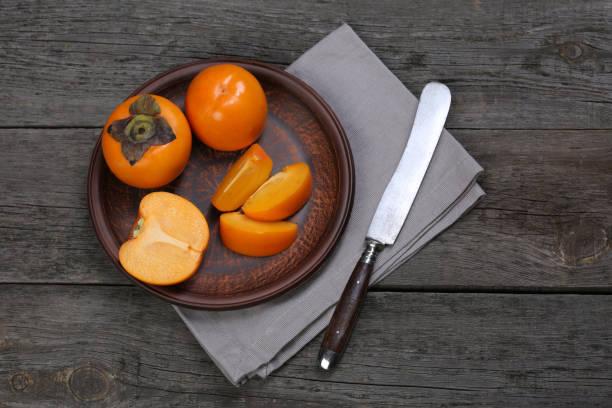 japanische kaki in keramikplatte auf holztisch - sharonfrucht stock-fotos und bilder