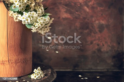 Japanese philosophy Wabi Sabi background. White small flowers spirea with falling petals in a brown wooden vase on vintage rusty background