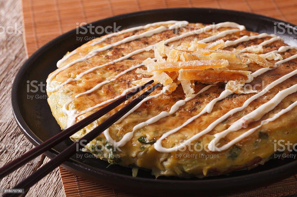 Japanese pizza: okonomiyaki on a plate and chopsticks. horizontal stock photo