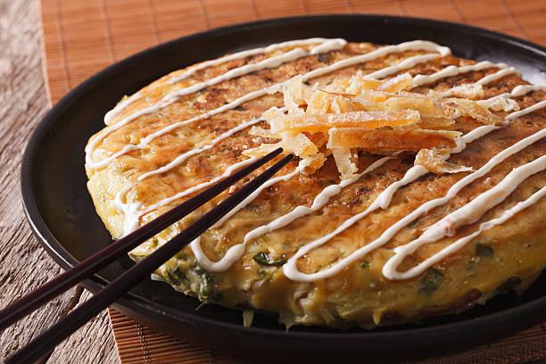 japanische pizza :  hin zur einheimischen spezialität okonomiyaki auf einem teller und stäbchen. horizontale - teppan yaki grill stock-fotos und bilder