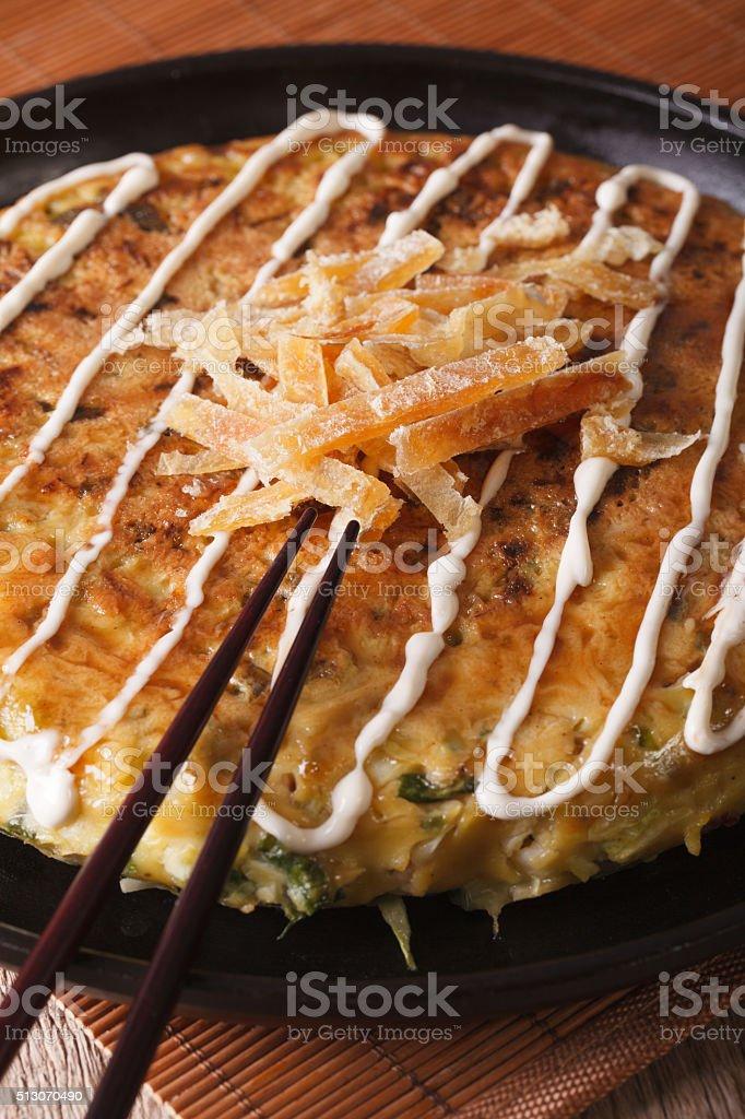 Japanese pizza: okonomiyaki on a plate and chopsticks. Vertical stock photo