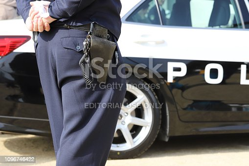 istock Japanese police officer with patrol car 1096746422