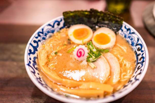 日本のラーメンの汁、鶏、卵、アサツキ、暗い背景の木の新芽 - ラーメン ストックフォトと画像