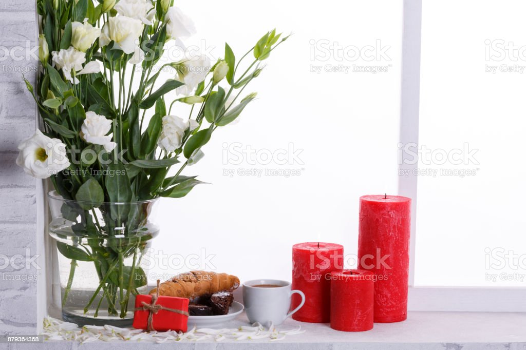 Japanese Roses In A Vase Of Water Near Candles And Breakfast On The