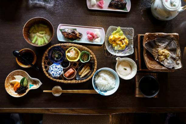 白いご飯、焼き魚、目玉焼き、スープ、明太子、漬物、海藻、ホット プレート、他のおかず、木製のテーブルに緑茶など日本旅館の朝食料理が調理しました。 - 和食 ストックフォトと画像