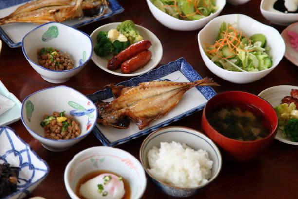 日本旅館の朝食料理など調理白いご飯、焼き魚、ゆで卵、味噌汁、納豆、その他のおかず - 和食 ストックフォトと画像