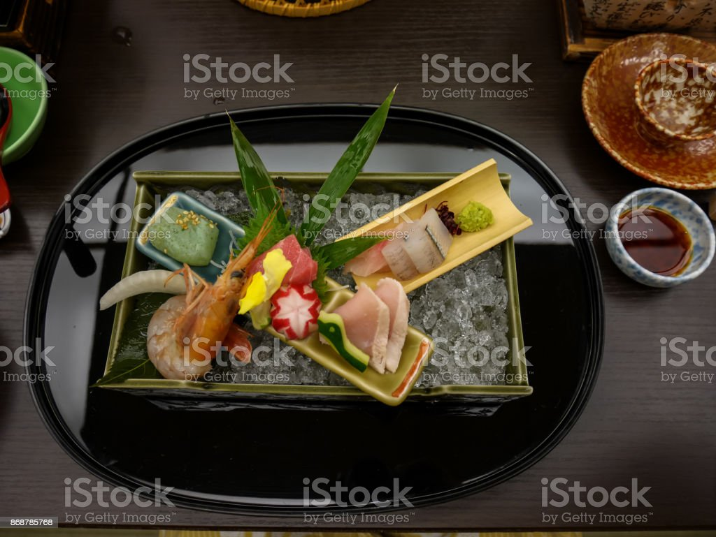 Japanese ryokan kaiseki dinner decorative sashimi set including Pacific blue fin tuna, shrimp, greater amberjack, halfbeak, konjac in ooishi on crushed ice tray with wasabi and soy sauce stock photo