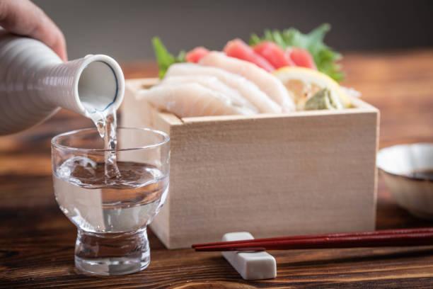 japanese sake and sashimi in wooden box, masu stock photo