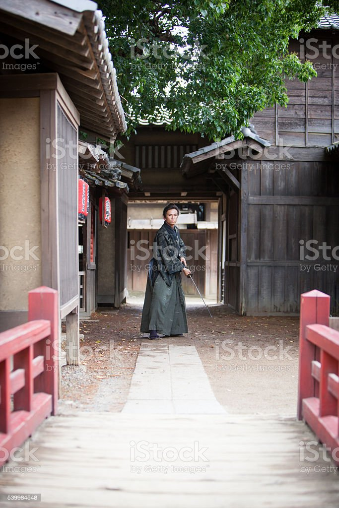 Japanese Samurai stands ready with sword in hand stock photo