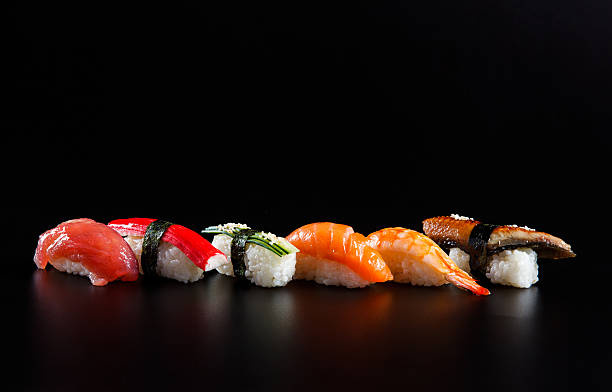 japanese seafood sushi, on black background - japanese food stock photos and pictures