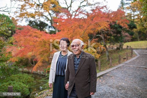 Japanese senior couple walking in autumn foliage