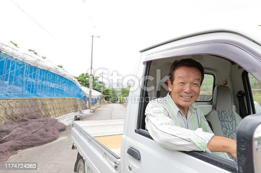 Japanese Senior man driving small truck