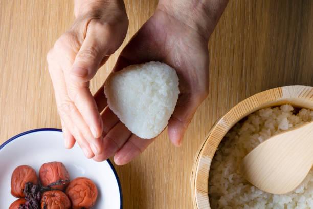 日本の先輩女性がおにぎりを持ち、お米を梅干で煮込んだもの - 日本食 ストックフォトと画像