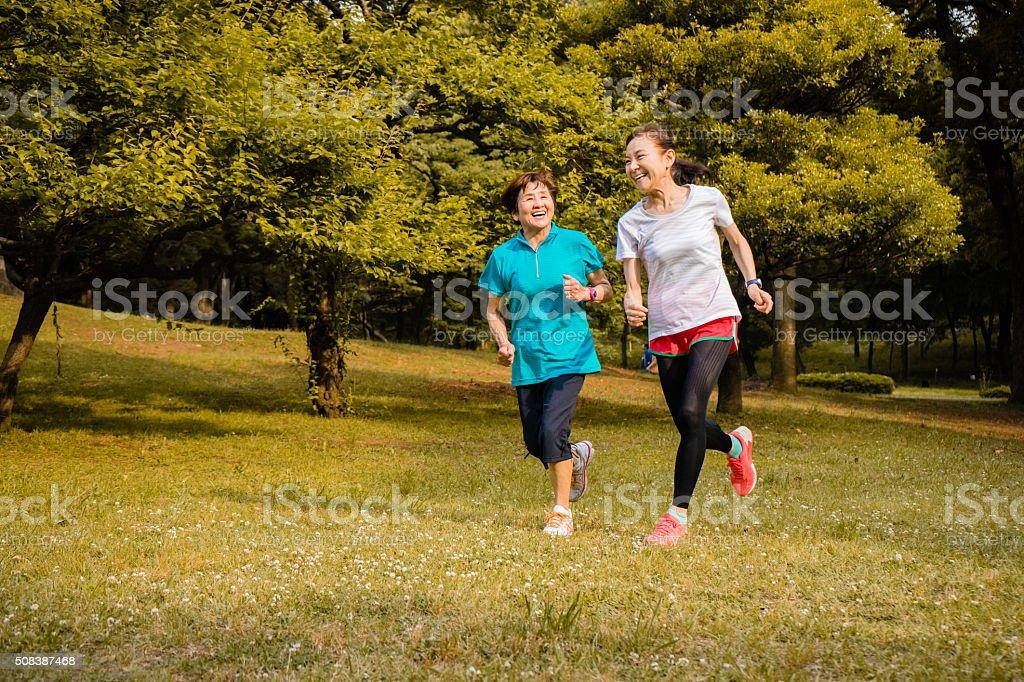 Japanese senior women running in the park stock photo