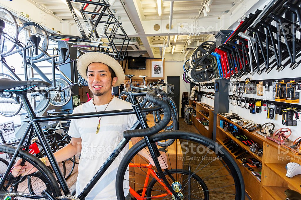 Japanese Small Businessman Holding a Bicycle in his Bike Shop圖像檔