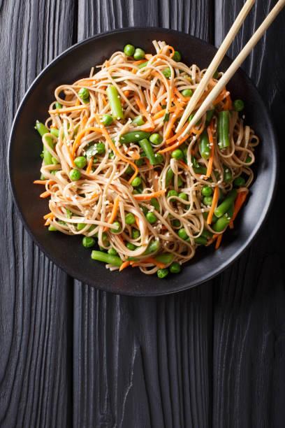japanse soba salade met groenten en sesam close-up op tafel. verticale bovenaanzicht - sobanoedels stockfoto's en -beelden