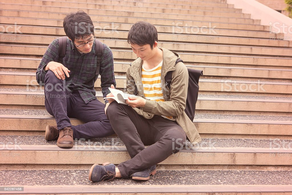 japanese student classmates checking books at stairs in kyoto japan stock photo