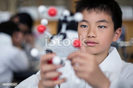 istock Japanese student holding a molecular model 490858342