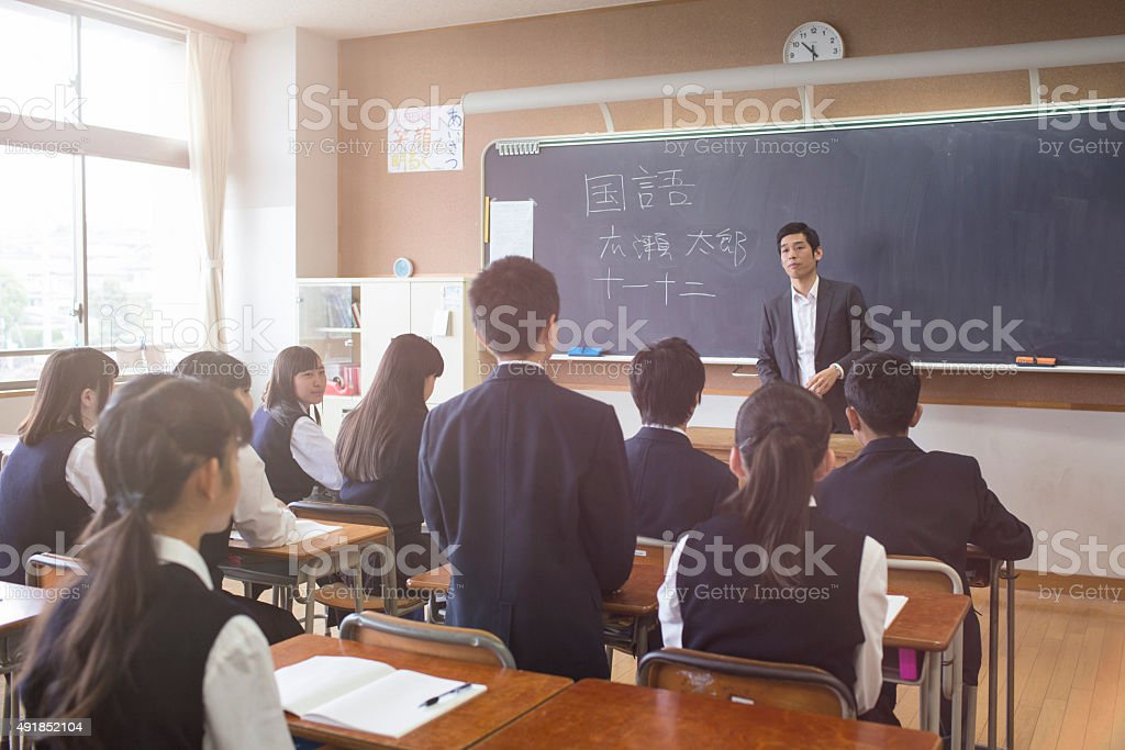 Japanese student stand answering a question to his teacher stock photo