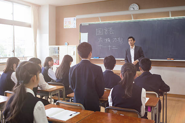 日本の学生スタンド回答質問に彼の教師 - 制服 ストックフォトと画像