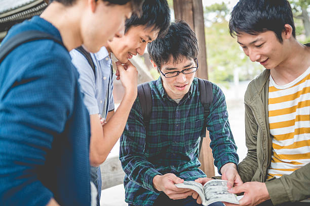 japanese students reading manga, chion-ji temple park, kyoto, japan, asia - manga style stock photos and pictures