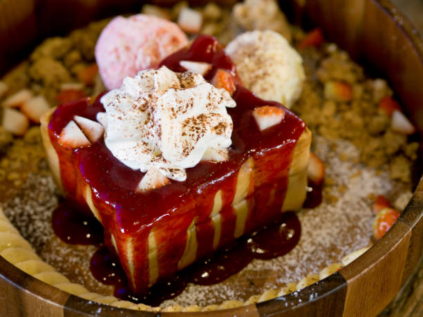 Japanese style bakery or dessert, butter honey toast served with strawberry and vanilla ice cream scoops decorated with fresh strawberry, banana, crumbs on wooden dish and wooden table stock photo