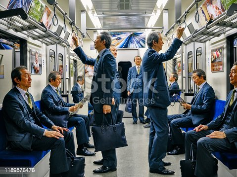 A crowd of passengers that are all the same man on a Japanese subway train. Fully property released location.